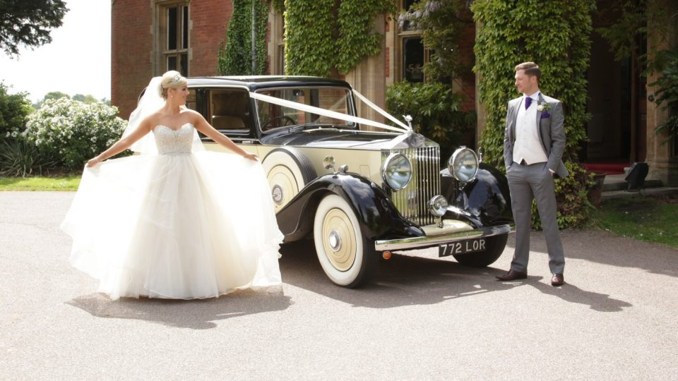Hertfordshire bride and groom outside building with car