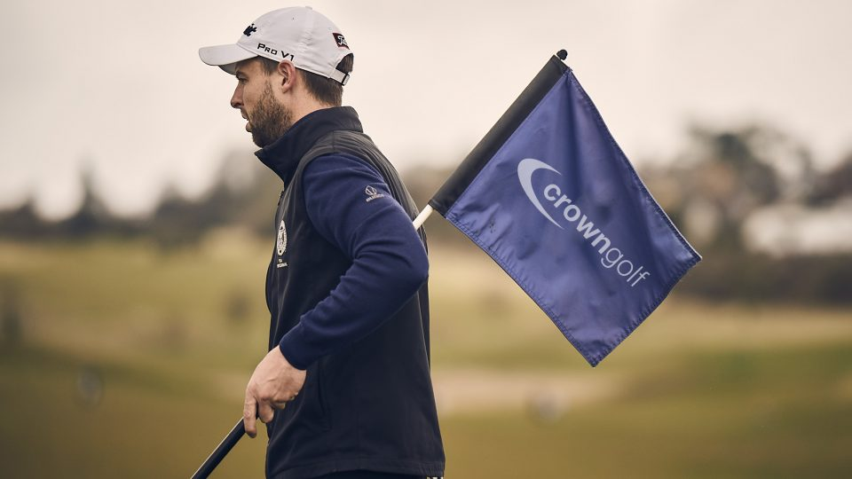 golfer holding crown golf flag